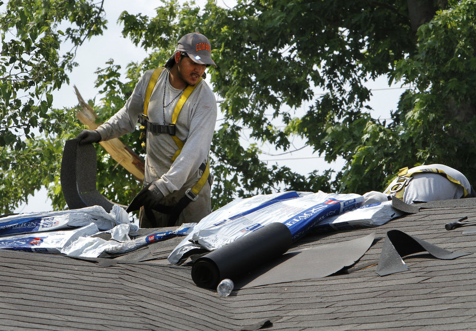 Photo - A roofer applies material to a roof of a house near Telephone Road on Tuesday in Moore.  Photo by Steve Sisney, The Oklahoman  STEVE SISNEY