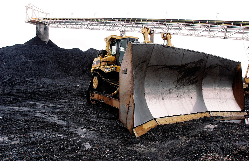 Photo - FILE - In this March 9, 2006 file photo, a large dozer sit ready for work at Peabody Energy's Gateway Coal Mine near Coulterville, Ill. A 10 percent reduction in carbon dioxide emissions will mean a decline of 180 million tons, or 18 percent, in U.S. coal production, according to Bernstein Research. That would hurt miners such as Peabody Energy, Alpha Natural Resources and Arch Coal. (AP Photo/Seth Perlman, File)