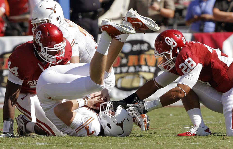 Oklahoma's Jeremy Beal (44) and Travis Lewis (28) roll up Texas quarterback Garrett Gilbert (7) in the first half of the Red River Rivalry college football game between the University of Oklahoma Sooners (OU) and the University of Texas Longhorns (UT) at the Cotton Bowl on Saturday, Oct. 2, 2010, in Dallas, Texas.   Photo by Chris Landsberger, The Oklahoman
