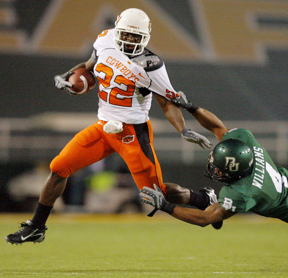 OSU's Dantrell Savage (22) tries to get away from the tackle attempt by Baylor's Jeremy Williams (4) in the first half during the college football game between Oklahoma State University and Baylor University at Floyd Casey Stadium in Waco, Texas, Saturday, Nov. 17, 2007. BY MATT STRASEN, THE OKLAHOMAN