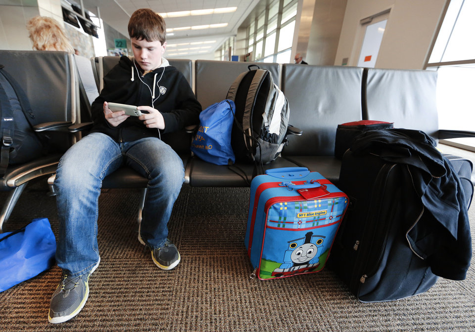 Nicholas Lintz, 14, waits for a flight to Orlando, Fla., at Will Rogers World Airport in Oklahoma City. Lintz is on spring break and going to Disney World with his family. Photo by Steve Gooch, The Oklahoman