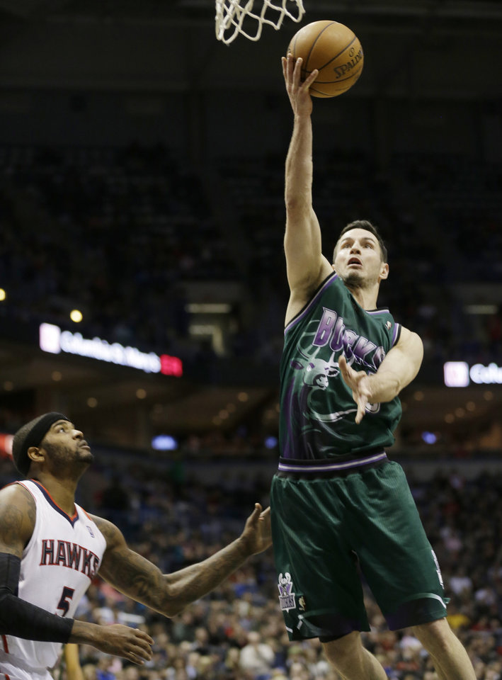 Photo - Milwaukee Bucks' J.J. Redick puts up a shot against Atlanta Hawks' Josh Smith (5) during the second half of an NBA basketball game, Saturday, Feb. 23, 2013, in Milwaukee. (AP Photo/Jeffrey Phelps)