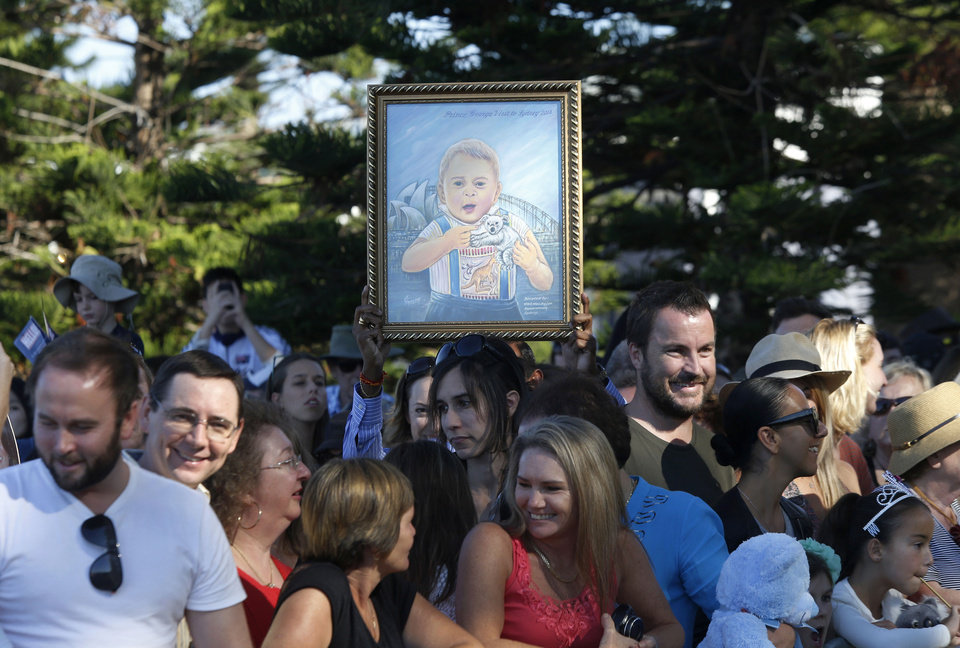 A supporter of Britain's Prince William and his wife Kate, Duchess of Cambridge, holds up a frame painting of their son Prince George featuring a koala and kangaroo before William's and Kate's visit to a surf lifesaving demonstration at Sydney's Manly Beach, Friday, April 18, 2014. The Royal couple are undertaking a 19-day official visit to New Zealand and Australia with their son, George.  (AP Photo/Jason Reed, Pool)