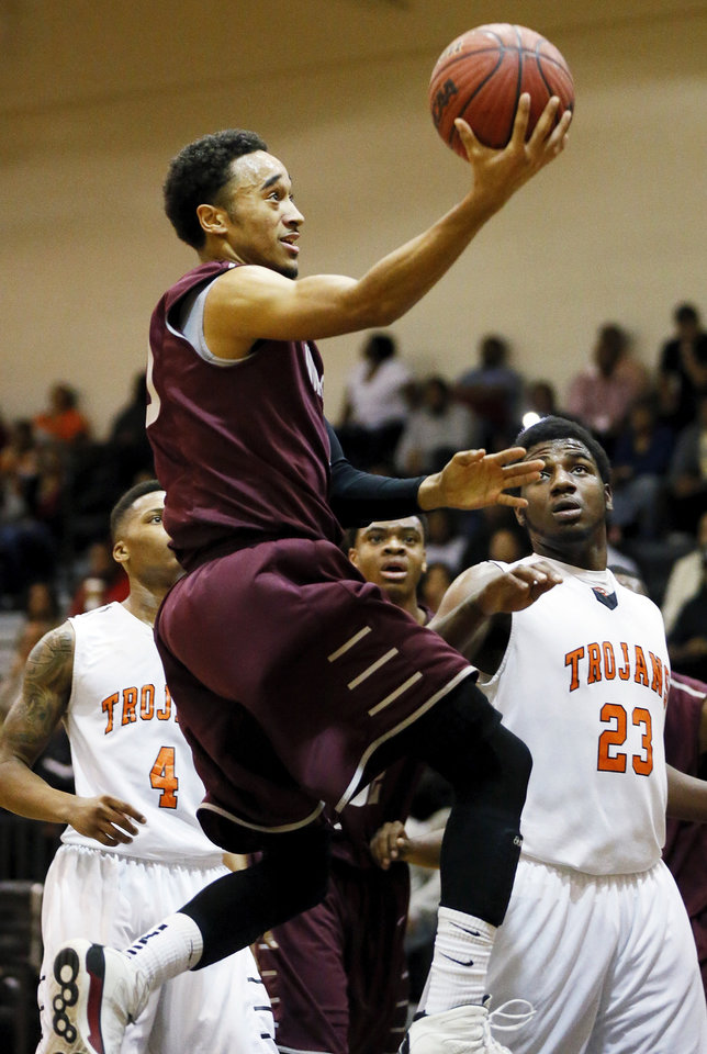 Shawndale Pina (10) of Northeast takes the ball to the hoop next to Deondre Clark (23) of Douglass during a boys high school basketball game between Douglass and Northeast at Douglass High School in Oklahoma City, Friday, Feb. 8, 2013. Photo by Nate Billings, The Oklahoman
