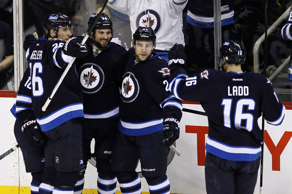 Photo - Winnipeg Jets' Zach Bogosian (44), Bryan Little (18), Blake Wheeler (26), Grant Clitsome (24) and Andrew Ladd (16) celebrate Bogosian's goal against the Carolina Hurricanes during the first period of their NHL hockey game in Winnipeg, Manitoba, Thursday, April 18, 2013. (AP Photo/The Canadian Press, John Woods)