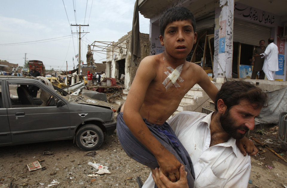 A Pakistani helps an injured boy at the site of car bombing on the outskirts of Peshawar, Pakistan, Sunday, June 2013. A car bomb exploded as a convoy of paramilitary troops passed through the outskirts of the northwest Pakistani city of Peshawar, killing more than a dozen people and wounding scores of others, police said.(AP Photo/Mohammad Sajjad)