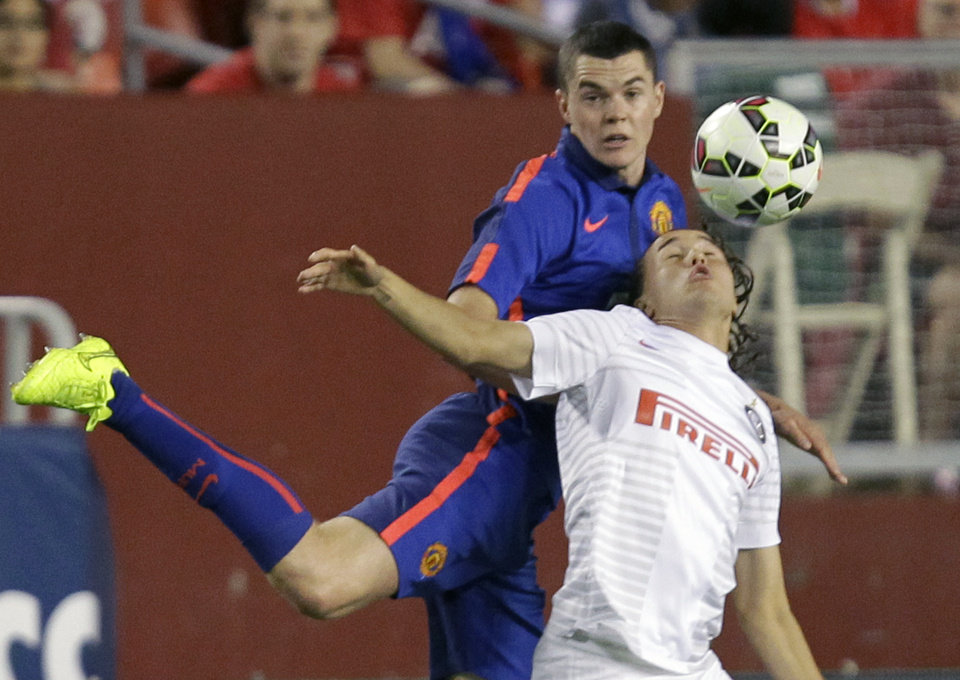 Photo - Inter Milan's Diego Laxalt, front, and Manchester United's Michael Keane battle for the ball during the second half of the 2014 Guinness International Champions Cup soccer game, Tuesday, July 29, 2014, in Landover, Md.  Manchester United won 5-3 in a penalty kick shootout. (AP Photo/Luis M. Alvarez)