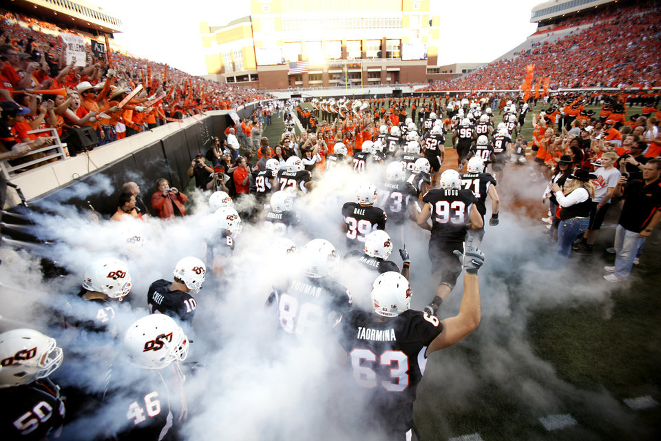 Photo - OSU runs on to the field before the college football game between Texas A&M University (TAMU) and Oklahoma State University (OSU) at Boone Pickens Stadium in Stillwater, Okla., Thursday, Sept. 30, 2010. Photo by Sarah Phipps, The Oklahoman