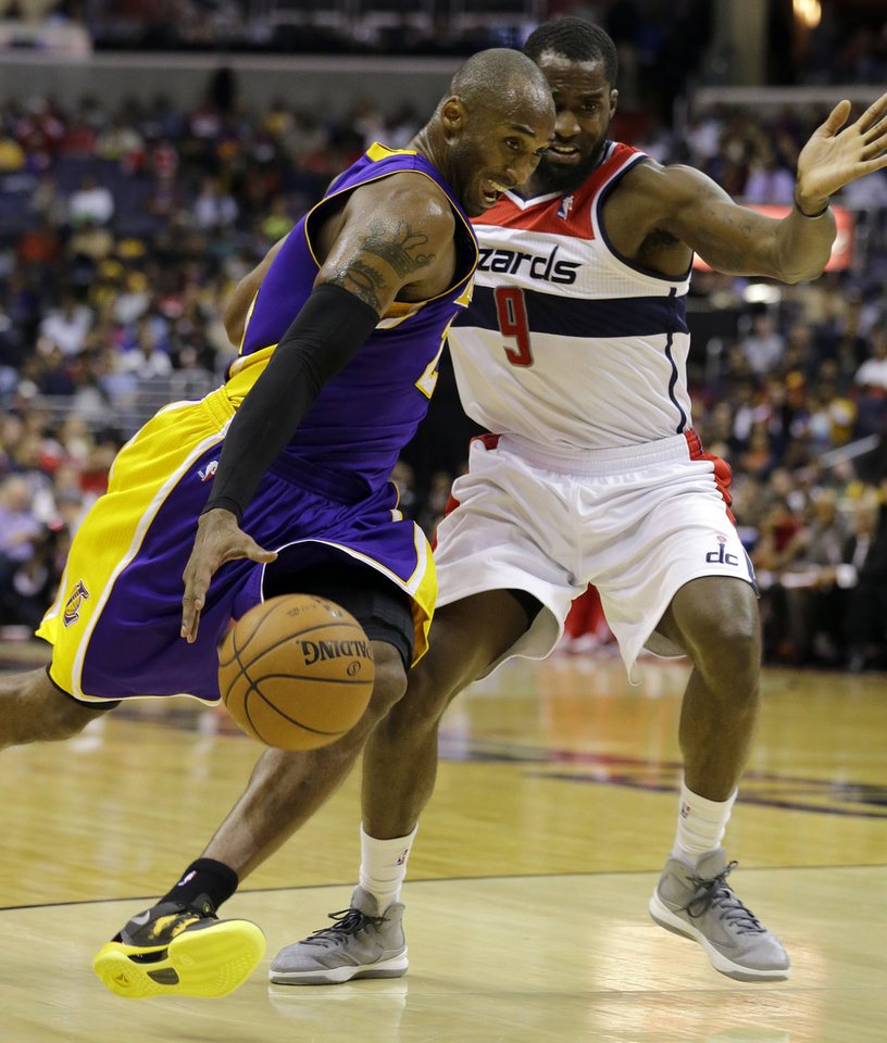 Photo - Los Angeles Lakers guard Kobe Bryant drives against Washington Wizards forward Martell Webster in the first half of an NBA basketball game Friday, Dec. 14, 2012 in Washington. (AP Photo/Alex Brandon)