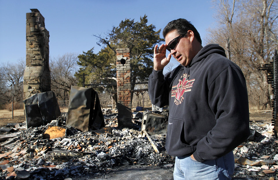 Chris Cochran walks through the charred rubble that was his family�s home in a rural area near Cashion until it was destroyed in a recent fire. His son, Cayden, a star player when he attended Cashion, will quarterback Valdosta State in the Division II national championship game on Saturday.  Photo by Jim Beckel, The Oklahoman