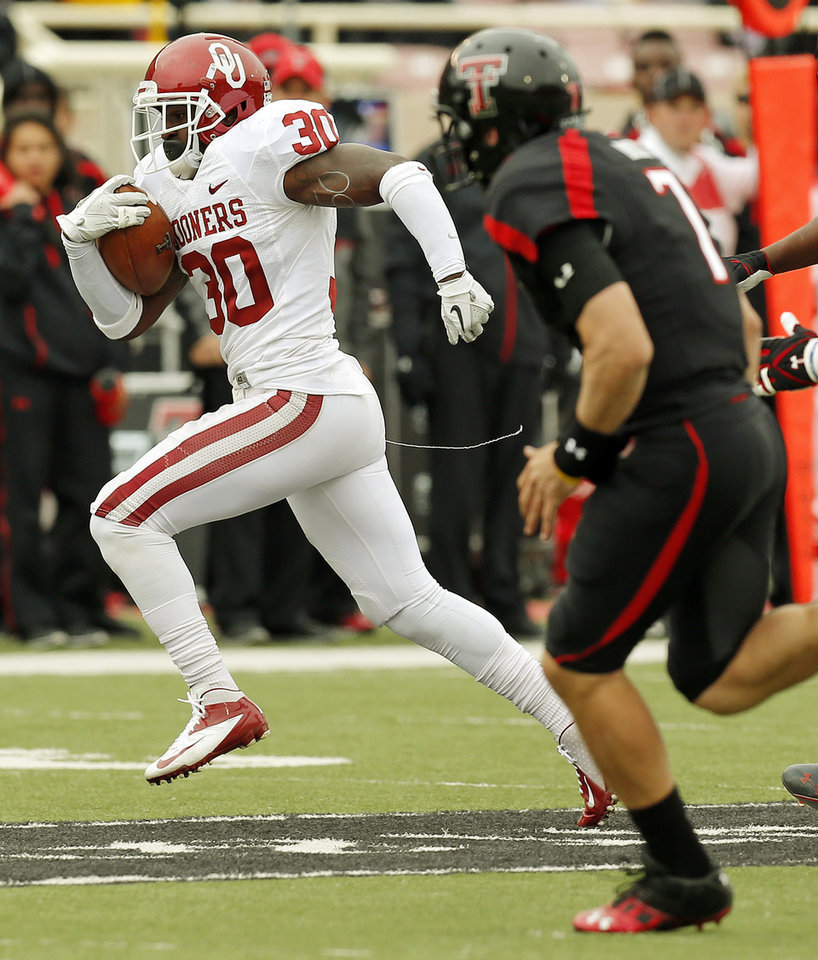 Oklahoma\'s Javon Harris (30) returns an interception of a pass by Texas Tech\'s Seth Doege (7), right, in the third quarter during a college football game between the University of Oklahoma (OU) and Texas Tech University at Jones AT&T Stadium in Lubbock, Texas, Saturday, Oct. 6, 2012. Harris returned the interception for a touchdown. Photo by Nate Billings, The Oklahoman