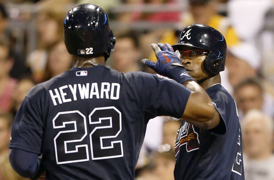 Photo - Atlanta Braves' B.J. Upton, right, greets Jason Heyward (22) after they scored on a single by Justin Upton in the fifth inning of a baseball game against the Pittsburgh Pirates on Tuesday, Aug. 19, 2014, in Pittsburgh. (AP Photo/Keith Srakocic)