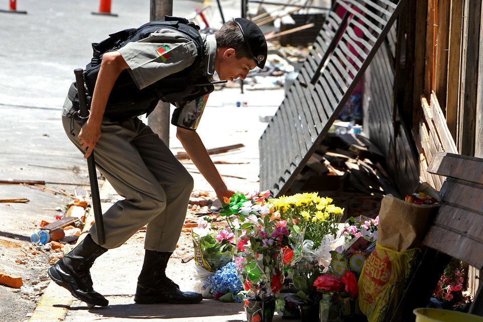 A police officer places flowers outside the Kiss nightclub that were brought by mourners in memory of those who died due to a fire at the club in Santa Maria, Brazil, Monday, Jan. 28, 2013.  A fast-moving fire roared through the crowded, windowless Kiss nightclub in this southern Brazilian city early Sunday, killing more than 230 people. Many of the victims were under 20 years old, including some minors. (AP Photo/Nabor Goulart) ORG XMIT: XSI106