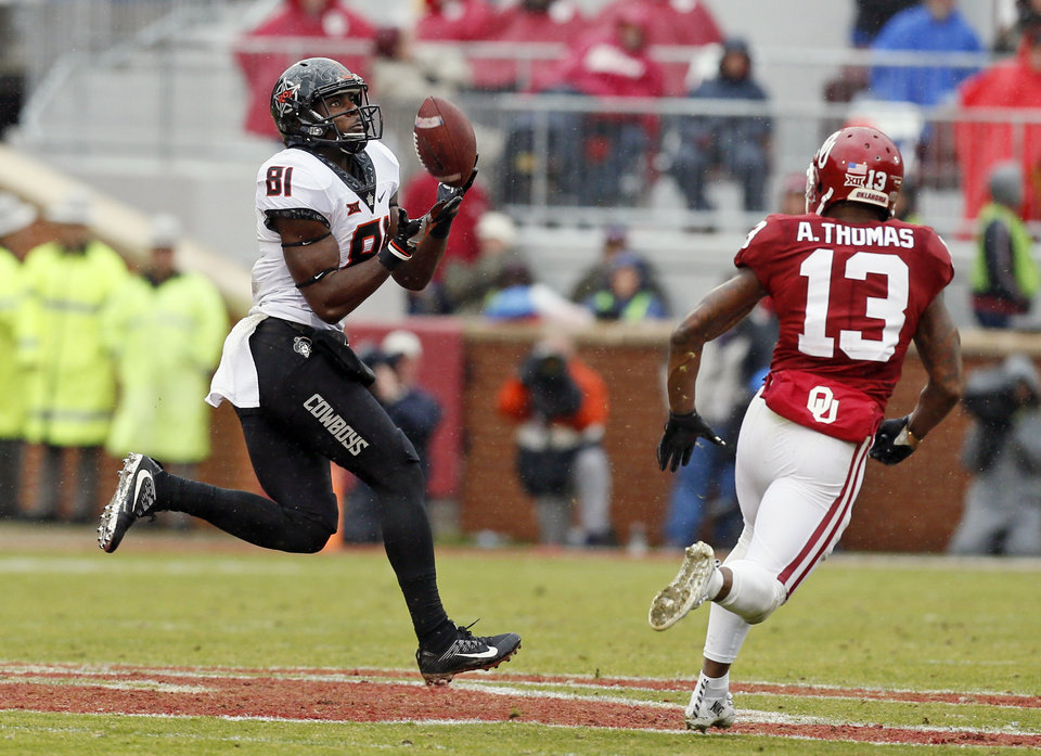 Photo - Oklahoma State's Jhajuan Seales (81) makes a catch near Oklahoma's Ahmad Thomas (13) in the third quarter during the Bedlam college football game between the Oklahoma Sooners (OU) and the Oklahoma State Cowboys (OSU) at Gaylord Family - Oklahoma Memorial Stadium in Norman, Okla., Saturday, Dec. 3, 2016. OU won 38-20. Photo by Nate Billings, The Oklahoman
