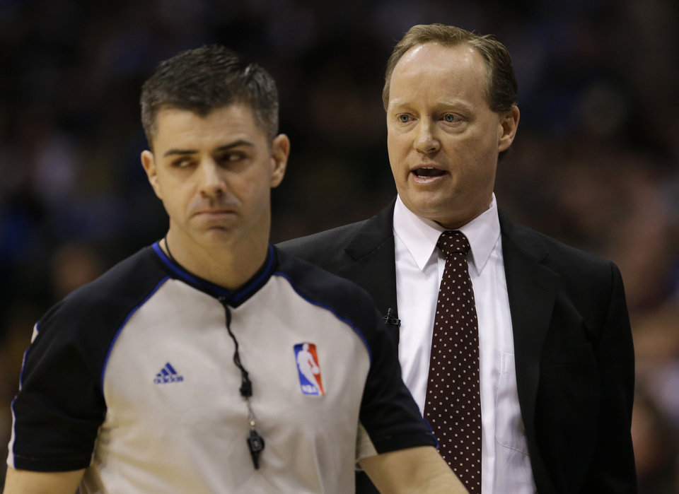 Photo - Referee Eli Roe, left, walks away as San Antonio Spurs acting coach Mike Budenholzer, right, complains about a play against the Dallas Mavericks in the first half of an NBA basketball game on Friday, Jan. 25, 2013, in Dallas. Spurs head coach Greg Popovich was absent from the game.  (AP Photo/Tony Gutierrez)