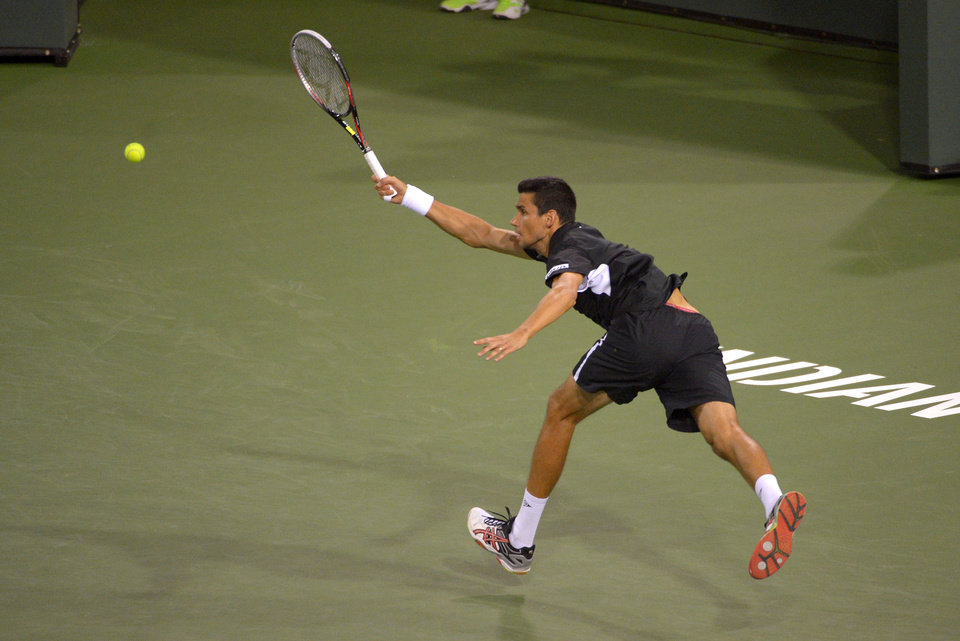 Photo - Victor Hanescu, of Romania, returns a shot to Novak Djokovic, of Serbia, during their match at the BNP Paribas Open tennis tournament, Sunday, March 9, 2014, in Indian Wells, Calif. (AP Photo/Mark J. Terrill)