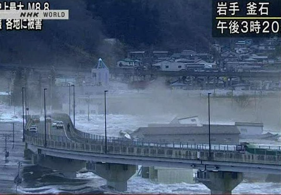 Photo - In this video image taken from Japan's NHK TV, a tsunami surge sweeps water under a highway in Kamaishi, Iwate Prefecture, Japan Friday March 11, 2011 following a massive earth quake. A magnitude 8.9 earthquake slammed Japan's northeastern coast Friday, unleashing a 13-foot (4-meter) tsunami that swept boats, cars, buildings and tons of debris miles inland. Fires triggered by the quake burned out of control up and down the coast.  (AP PHOTO/NHK TV) MANDATORY CREDIT, JAPAN OUT, TV OUT,  NO SALES, EDITORIAL USE ONLY ORG XMIT: LON829