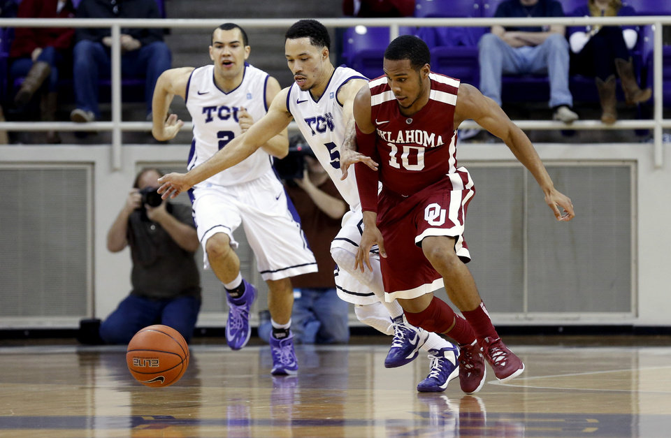 Photo - TCU guard Kyan Anderson (5) and Oklahoma guard Jordan Woodard (10) scramble for a loose ball in the first half of an NCAA basketball game Saturday, March 8, 2014, in Fort Worth, Texas. Oklahoma won 97-67. (AP Photo/Sharon Ellman)