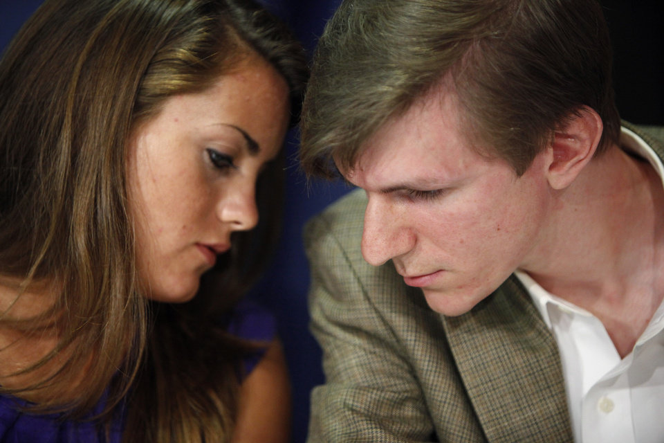This Oct. 2009 file photo shows Hannah Giles, left, talking with James O'Keefe III during a news conference at the National Press Club in Washington. The conservative activist whose hidden camera videos led to the downfall of the community group ACORN has settled a lawsuit with a former ACORN employee who appeared in them. In documents filed in a San Diego court, James O'Keefe agreed to pay Juan Carlos Vera $100,000 and apologized for any pain Vera suffered. (AP Photo/Haraz N. Ghanbari, file)