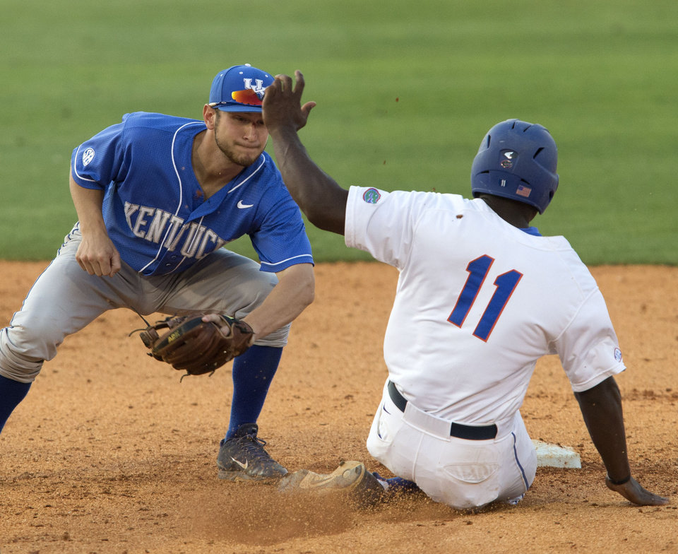 Photo - Florida's Josh Tobias is tagged out by Kentucky's Matt Reida on a steal attempt during the Southeastern Conference NCAA college baseball tournament Wednesday, May 21, 2014, in Hoover, Ala. (AP Photo/Hal Yeager)