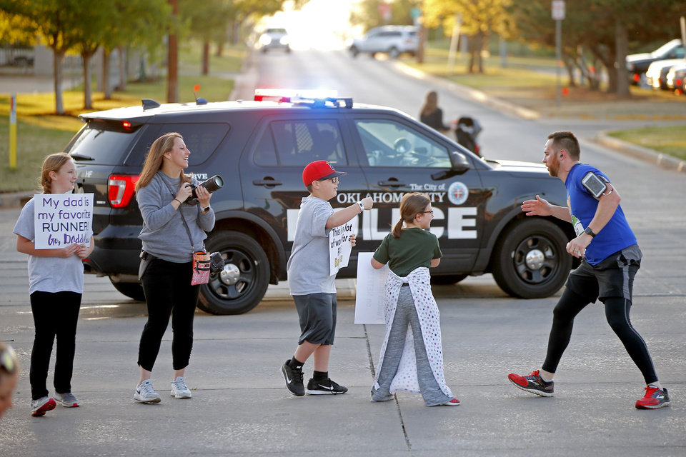 Photo - Runner David Frazier greets his wife Megan Frazier, daughters Cadence Frazier, 11, far left,  Hadlee Frazier, 7, and son Blake Frazier, 9,  on Lincoln Blvd. during the Oklahoma City Memorial Marathon in Oklahoma City, Sunday, April 29, 2018. Photo by Bryan Terry, The Oklahoman