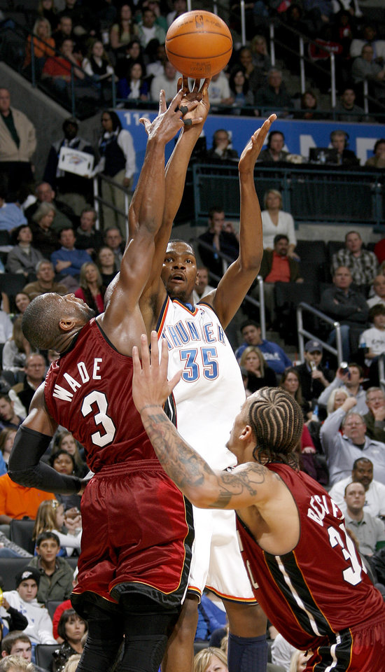 Photo - Oklahoma City's Kevin Durant shoots a basket between Miami's Dwyane Wade, left, and Michael Beasley during the NBA basketball game between the Oklahoma City Thunder and the Miami Heat at the Ford Center in Oklahoma City, Saturday, January 16, 2010. Photo by Bryan Terry, The Oklahoman