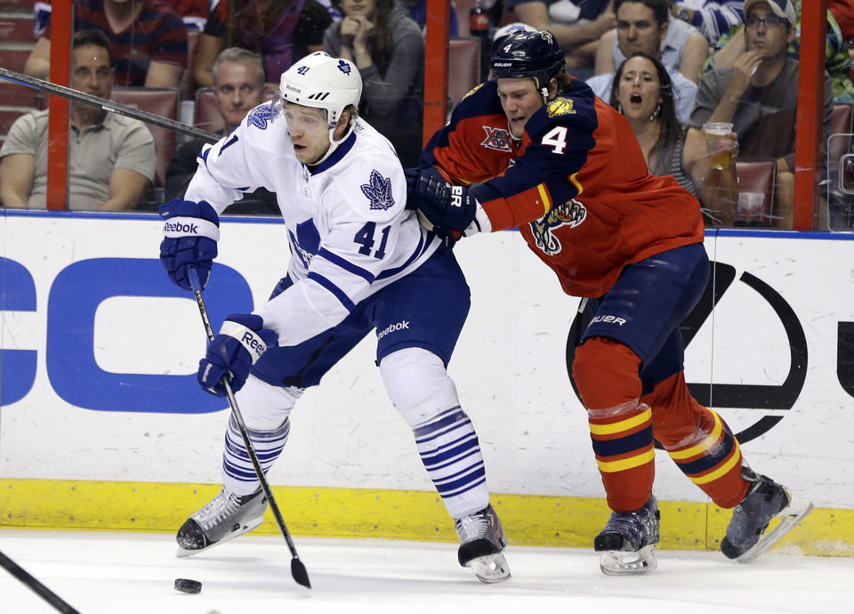 Photo - Toronto Maple Leafs left wing Nikolai Kulemin (41) prepares to shoot as Florida Panthers defenseman Dylan Olsen (4) moves in during the first period of an NHL hockey game on Thursday, April 10, 2014, in Sunrise, Fla. (AP Photo/Lynne Sladky)
