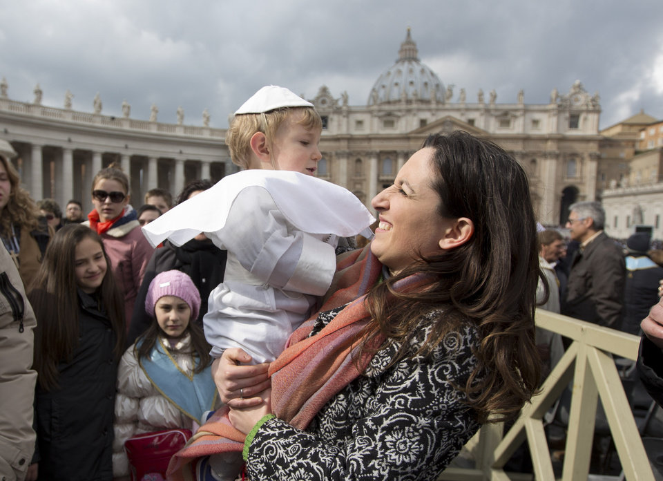 Photo - Paola Ciabattini smiles at her 19-month-old son Daniele De Sanctis, dressed up as a pope, during Pope Francis' weekly general audience in St. Peter's Square at the Vatican, Wednesday, Feb. 26, 2014. Francis kissed the child as the new must-have Carnival costume made its debut at the pope's general audience Wednesday. Daniele, who was crying, was hoisted up to Francis as he drove by in his open-topped jeep. During Carnival in Italy, children often go to school and spend their weekends dressed up in pirate, princess — and now pope — costumes. Carnival, also known as mardi gras, marks the period before the church's solemn Lenten season begins. Ciabattini said she dressed her son as a pope in a demonstration of affection towards Pope Francis. (AP Photo/Alessandra Tarantino)