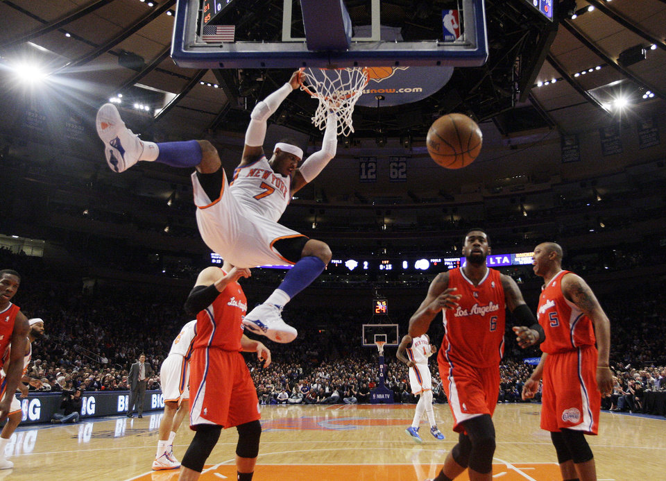 Photo -   New York Knicks' Carmelo Anthony (7) dunks the ball as Los Angeles Clippers' DeAndre Jordan chases down the ball during the first half of an NBA basketball game, Wednesday, April 25, 2012, in New York. (AP Photo/Frank Franklin II)