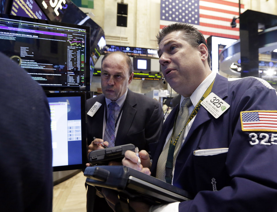 Photo - Traders Randy Beller, left, and William McInerney work on the floor of the New York Stock Exchange Thursday, April 10, 2014.  U.S. stock indexes are slipping lower in early trading Thursday as investors pick over a mixed batch of corporate earnings reports. (AP Photo/Richard Drew)