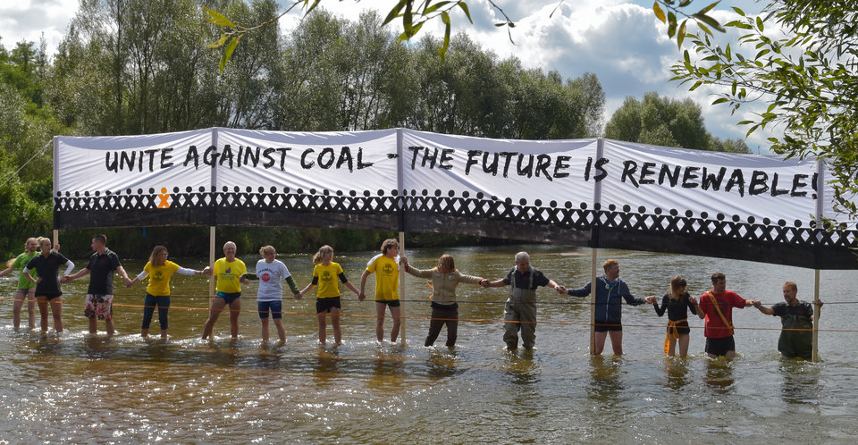 Photo - Demonstrators protest  with a human chain  against planned coal mines at the Neisse river ,  German-Polish border near Gross Gastrose, Germany Saturday Aug. 23, 2014. Several  thousand people have formed a human chain across the German-Polish border in a  protest against open-cast mining for brown coal, also known as lignite, in the region.  (AP Photo/dpa, Patrick Pleul)