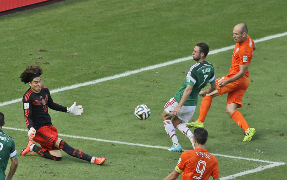 Photo - Mexico's goalkeeper Guillermo Ochoa, left, blocks a shot by Netherlands' Arjen Robben, right, during the World Cup round of 16 soccer match between the Netherlands and Mexico at the Arena Castelao in Fortaleza, Brazil, Sunday, June 29, 2014. (AP Photo/Themba Hadebe)