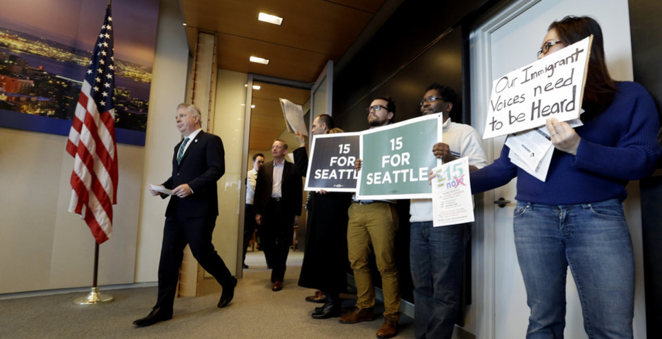Photo - Seattle Mayor Ed Murray, left, walks into a news conference past supporters and opponents of a proposal to increase the minimum wage in the city Thursday, April 24, 2014, in Seattle. The mayor said his advisory group of business, labor, non-profits and other representatives have not yet agreed on a plan to increase the minimum wage to $15 an hour. (AP Photo/Elaine Thompson)