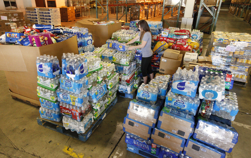 Photo - Volunteer Ashley Lehl (CQ Lehl), Okla. City, working near a large pile of donated water bottles as donations are being sorted at the Feed the Children warehouse, 29 N McCormick, in Oklahoma City Wednesday, May 22, 2013.  Photo by Paul B. Southerland, The Oklahoman