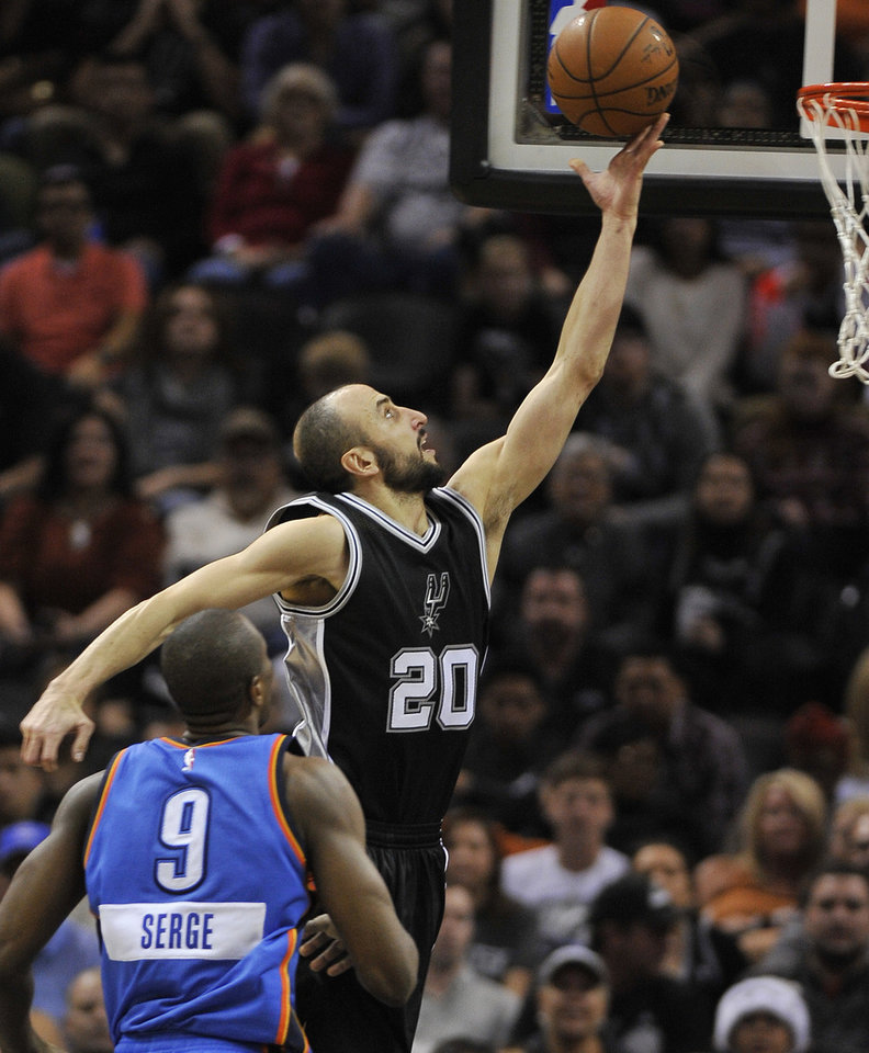 Photo - San Antonio Spurs guard Manu Ginobili (20), of Argentina, shoots against Oklahoma City Thunder forward Serge Ibaka during the second half of an NBA basketball game, Thursday, Dec. 25, 2014, in San Antonio. Oklahoma City won 114-106. (AP Photo/Darren Abate)