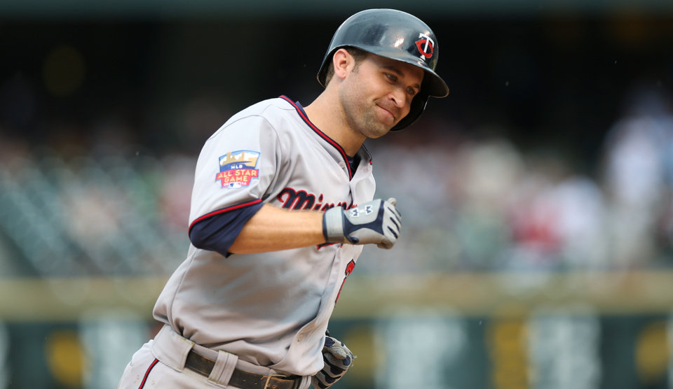 Photo - Minnesota Twins' Brian Dozier circles the bases after hitting a three-run home run against the Colorado Rockies in the ninth inning of the Twins' 13-5 victory in an interleague baseball game in Denver on Sunday, July 13, 2014. (AP Photo/David Zalubowski)