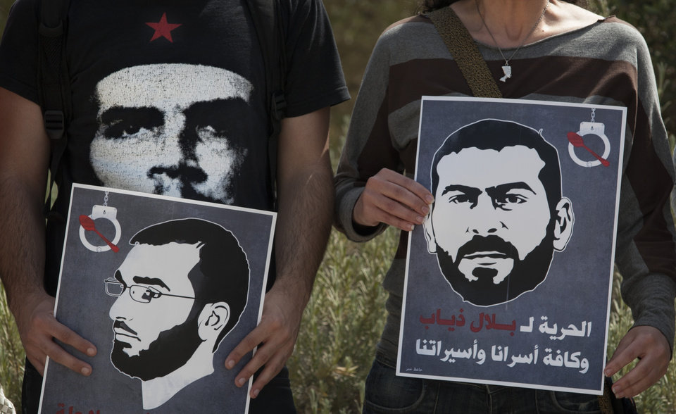 Photo -   Israeli Arab protestors hold posters depicting Palestinian prisoners on hunger strike, Thaer Halahleh, left, and Bilal Diab, right, as a hearing in their case takes place nearby in Israel's Supreme Court in Jerusalem Thursday, May 3, 2012. A Palestinian rights group said recently that half of about 5,000 Palestinian prisoners held by Israel are on a hunger strike, demanding an end to imprisonment without trial as well as better conditions.(AP Photo/Sebastian Scheiner)