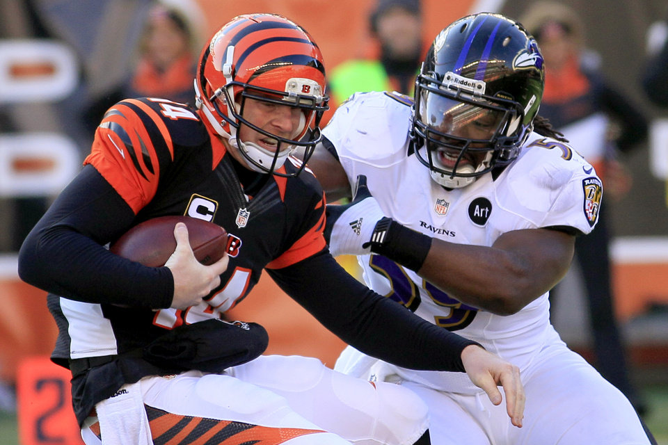 Photo - Cincinnati Bengals quarterback Andy Dalton (14) avoids a sack by Baltimore Ravens inside linebacker Dannell Ellerbe in the first half of an NFL football game, Sunday, Dec. 30, 2012, in Cincinnati. (AP Photo/Tom Uhlman)