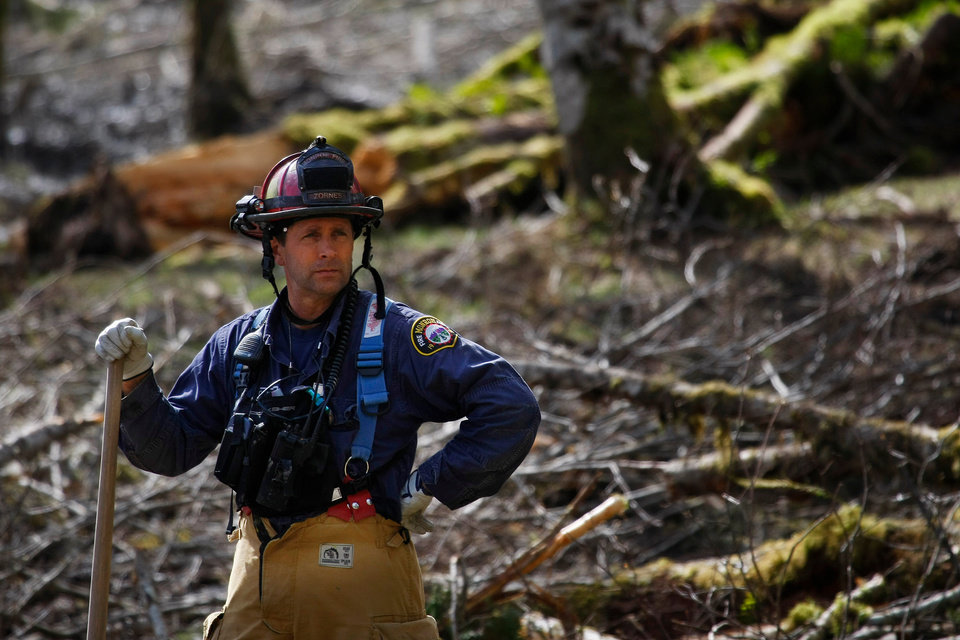 Photo - Capt. Jeff Zonrnes, of the Monroe Fire Department, looks on in the debris field, Wednesday, April 2, 2014, as volunteers worked to clear more of the mudslide area in Oso, Wash. A deadly mudslide in March killed more than two dozen people. (AP Photo/The Herald, Genna Martin)