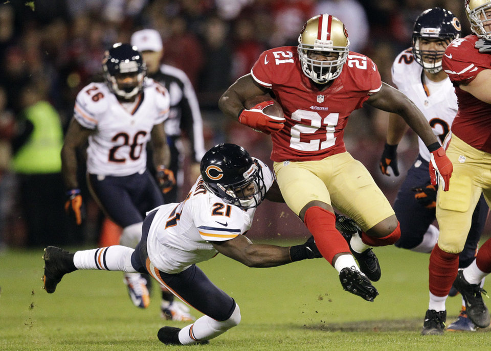 Photo -   San Francisco 49ers running back Frank Gore (21) leaps past Chicago Bears strong safety Major Wright (21) during the second quarter of an NFL football game in San Francisco, Monday, Nov. 19, 2012. (AP Photo/Tony Avelar)