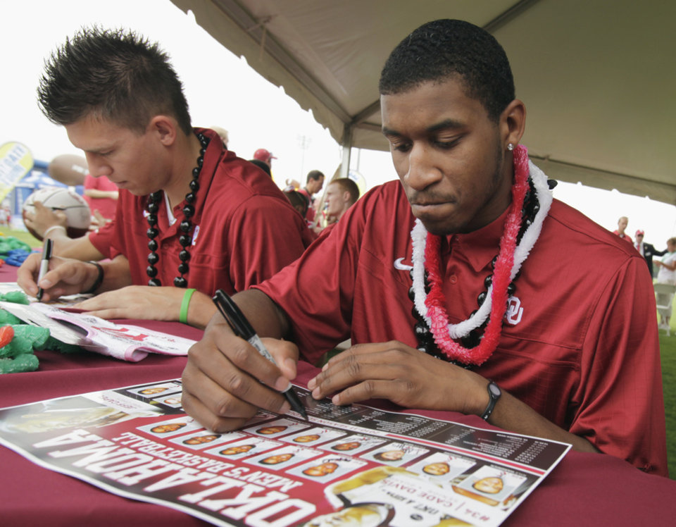 Photo - University of Oklahoma Basketball players Cade Davis (left) and Steven Pledger sign autographs during fan fest before the college football game between the University of Oklahoma Sooners (OU) and Florida State University Seminoles (FSU) at the Gaylord Family-Oklahoma Memorial Stadium on Saturday, Sept. 11 2010, in Norman, Okla.   Photo by Steve Sisney, The Oklahoman