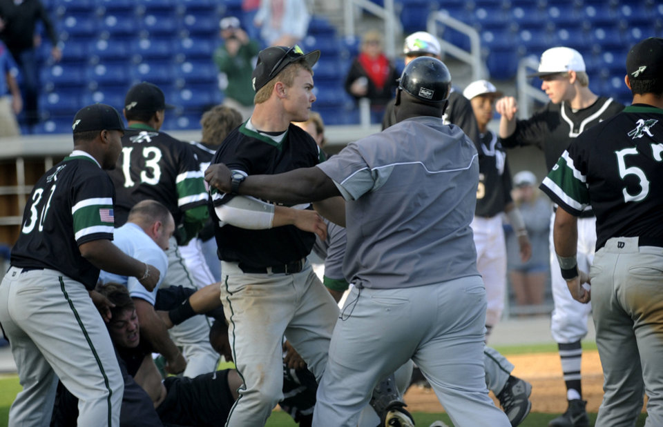 Photo - Members of the Norman North and Jacksonville Arlington Country Day baseball teams brawl at Maritime Park Stadium last week during the Tate Aggie Classic tournament.  PHOTOs BY PENSACOLA NEWS JOURNAL