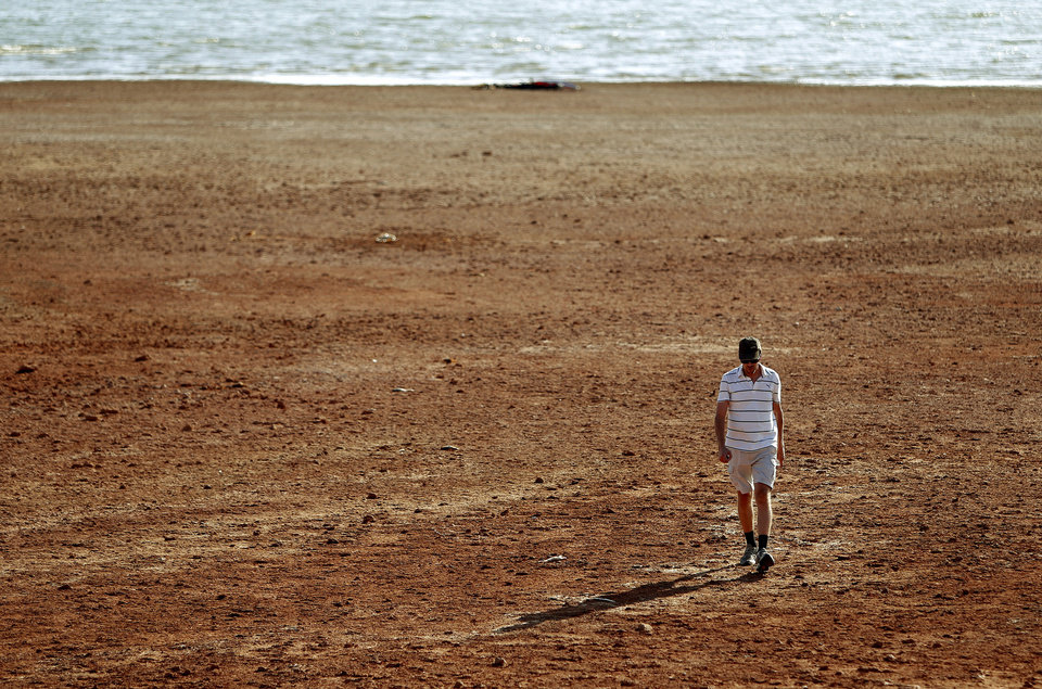 DROUGHT / LOW WATER LEVEL: Paul Gilchrest of Oklahoma City walks across the receding shoreline of Lake Hefner in Oklahoma City, Thursday, August 2, 2012. Photo by Bryan Terry, The Oklahoman