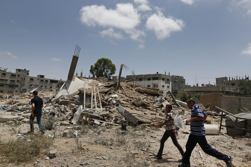 Photo - Palestinians walk past one of the houses of the al-Batsh family, demolished by an Israeli strike earlier last week, as they rush to the funeral procession of several members of the al-Batsh family who were killed in Saturday's Israeli airstrike, during a funeral procession in Gaza City on Sunday, July 13, 2014. The strike hit the home of Gaza police chief Taysir al-Batsh and damaged a nearby mosque as evening prayers ended Saturday, killing at least 18 people, wounding 50 and leaving some people believed to be trapped under the rubble, said Palestinian Health Ministry official Ashraf al-Kidra. (AP Photo/Lefteris Pitarakis)