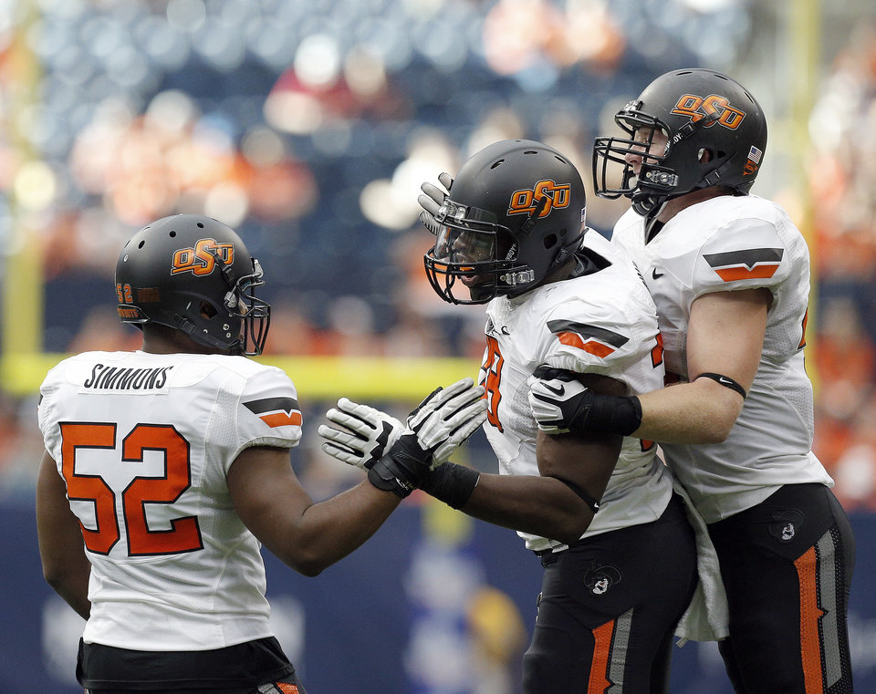 Oklahoma State's Ryan Simmons (52), Emmanuel Ogbah (38) and Caleb Lavey (45) celebrate a Ognah sack during second half of the AdvoCare Texas Kickoff college football game between the Oklahoma State University Cowboys (OSU) and the Mississippi State University Bulldogs (MSU) at Reliant Stadium in Houston, Saturday, Aug. 31, 2013. Photo by Sarah Phipps, The Oklahoman
