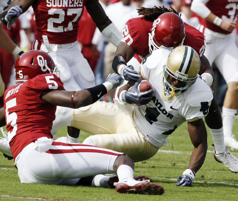 Photo - Joseph Ibiloye (5) and Quinton Carter bring down receiver David Gettis during the first half of the college football game between The University of Oklahoma Sooners (OU) and the Baylor Bears at the Gaylord Family-Oklahoma Memeorial Stadium on Saturday, Oct. 10, 2009, in Norman, Okla.