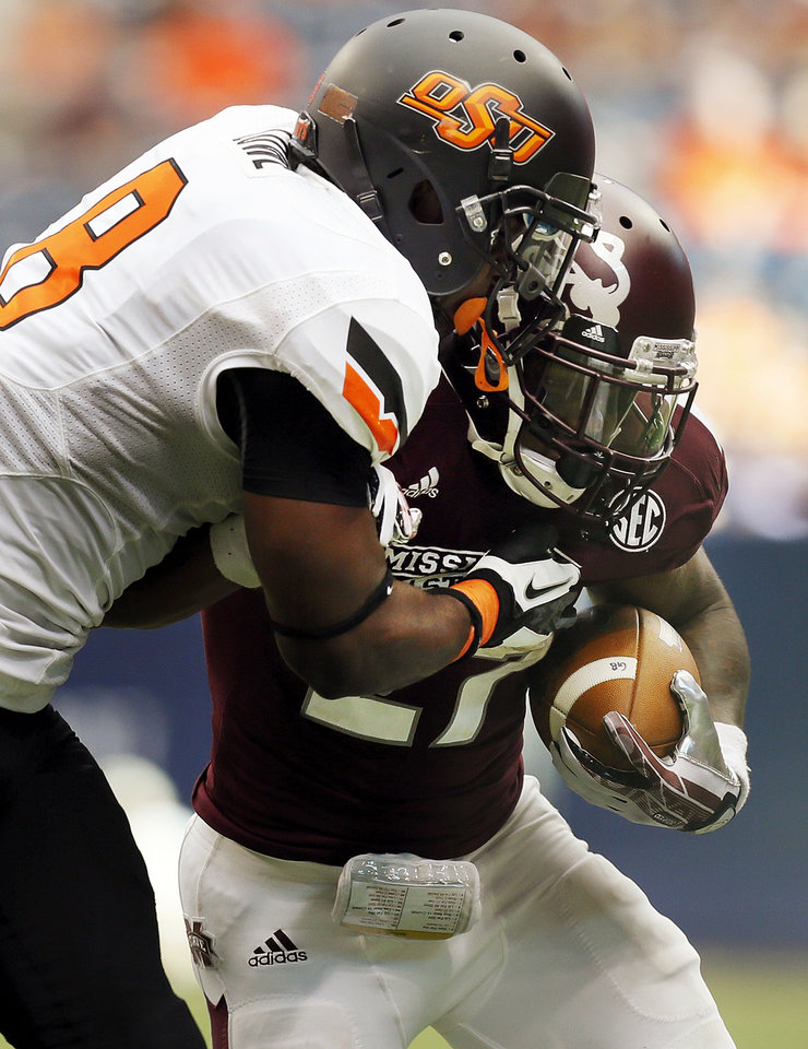 Photo - Oklahoma State's Daytawion Lowe (8) stops Mississippi State's LaDarius Perkins (27) for a loss on the play in the fourth quarter during the AdvoCare Texas Kickoff college football game between the Oklahoma State University Cowboys (OSU) and the Mississippi State University Bulldogs (MSU) at Reliant Stadium in Houston, Saturday, Aug. 31, 2013. OSU won, 21-3. Photo by Nate Billings, The Oklahoman