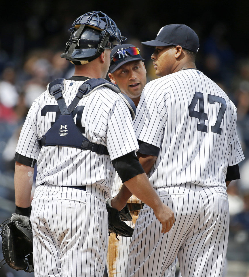 Photo - New York Yankees shortstop Derek Jeter, center, and Yankees catcher Brian McCann (34) talk to Yankees starting pitcher Ivan Nova (47) on the mound after Nova allowed three runs in the fourth inning of a baseball game against the Baltimore Orioles at Yankee Stadium in New York, Tuesday, April 8, 2014.  New York Yankees manager Joe Girardi took Nova out of the game moments later. (AP Photo/Kathy Willens)