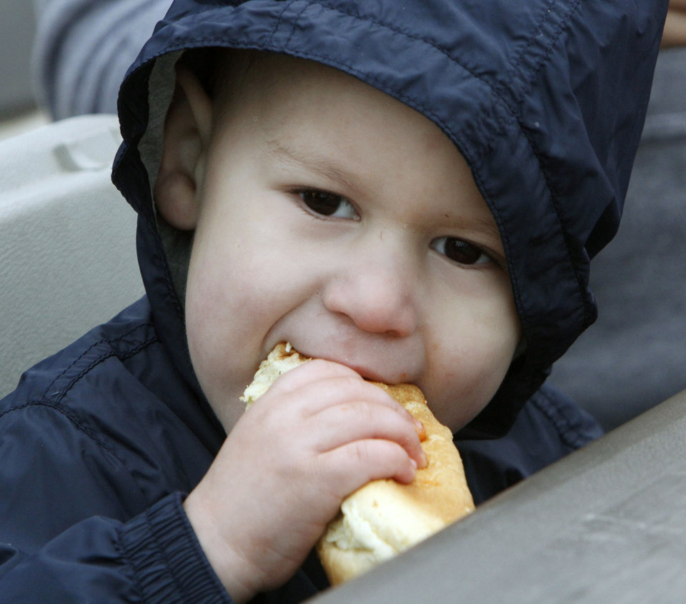 Three year old Miguel Angel Chavez eats a hot dog as LOVE OKC and Convoy of Hope distributed goods and services to metro residents at the old John Marshall High School in Oklahoma City, OK, Saturday, October 6, 2012. Services included groceries, consultations with health professionals, haircuts, family portraits, job fair, live entertainment and a free lunch for those in need.  By Paul Hellstern, The Oklahoman