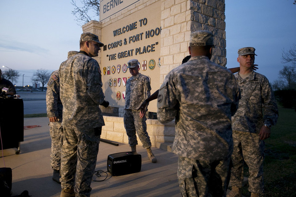 Photo - Military personnel wait for a news conference to begin at Fort Hood, Texas, on Wednesday, April 2, 2014. A gunman opened fire in an attack that left four people killed including the shooter, at the same post where more than a dozen people were killed in a 2009 mass shooting, law enforcement officials said. The gunman died of a self-inflicted gunshot wound, officials said. At least 14 people were hurt in the shooting. (AP Photo/Austin American-Statesman, Deborah Cannon)